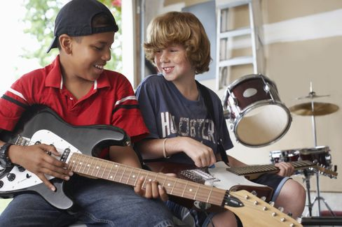 Two young teens learning to play guitar and drums